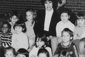 Black and white photograph of Brenda Spratt, principal of Union Mill from 1986 to 1997. She is seated on the steps outside of the main office and is surrounded by students.