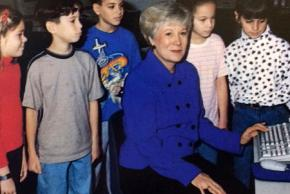 Color photograph of Carolyn Coleman, principal of Union Mill from 1997 to 2002. She is seated at a desk with a computer and is surrounded by students.